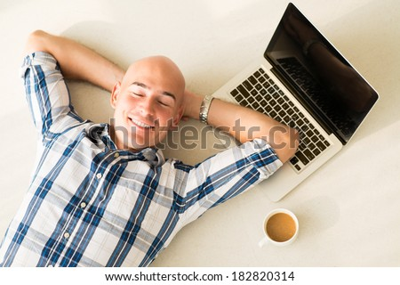 Above view of a businessman resting on the floor with smile after exhausted working day  - stock photo