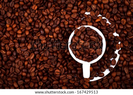 Above view of a coffee cup filled with coffe beans. Roasted coffee beans background.