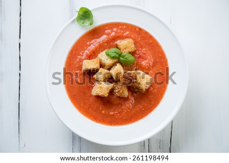 Above view of a glass plate with Gazpacho, white wooden surface - stock photo
