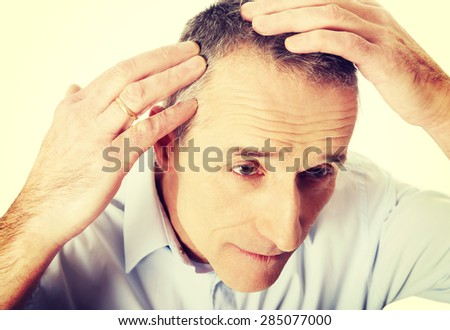 Above view of a man examining his hair. - stock photo