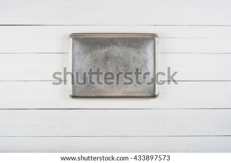 Above View of a Metal Cookie Sheet Cooking Pan Laying or Hung in center of a Rustic White or Gray Wood Board Background with room or space for copy, text, your words or ideas. Horizontal photo.