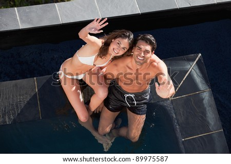 Above view of a smiling couple waving at the camera in a swimming pool - stock photo