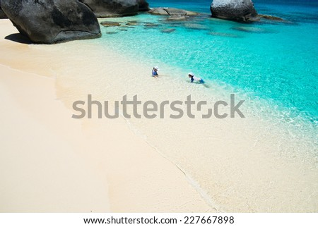 Above view of a stunning tropical ocean and white sand beach with kids splashing at shore