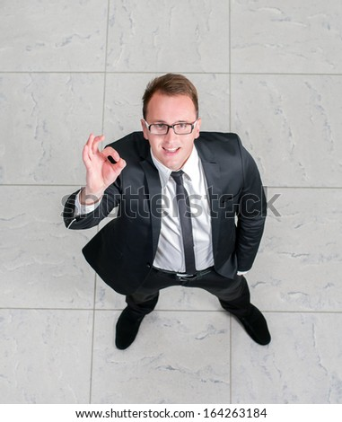 Above view of a successful businessman showing OK Sign. Top View - stock photo
