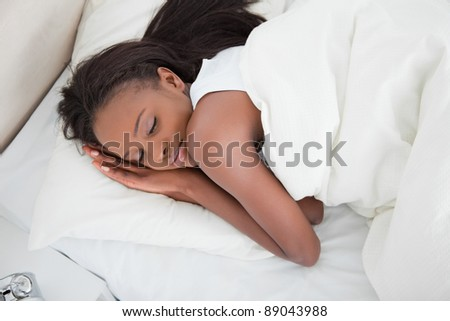 Above view of a young woman sleeping in her bedroom - stock photo