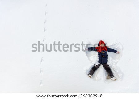 Above view of adorable little girl enjoying beautiful winter day making snow angel - stock photo