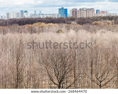 above view of bare trees in spring forest and urban houses - stock photo