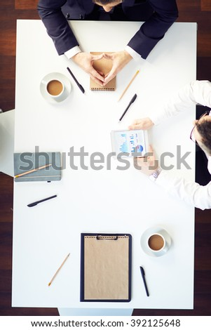Above view of business partners having a meeting at the table - stock photo