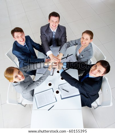Above view of business people with their hands on top of each other looking at camera - stock photo