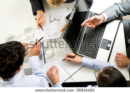 Above view of business people working with documents at meeting - stock photo