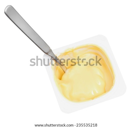 above view of caramel yogurt and spoon in disposable plastic cup isolated on white background - stock photo