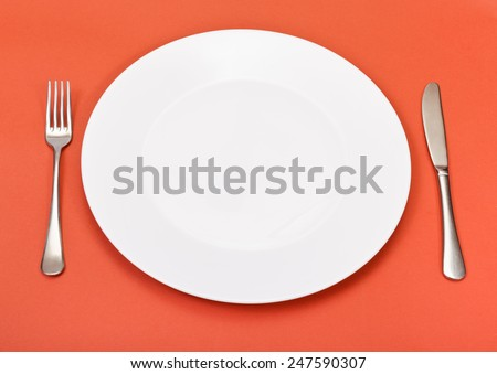 above view of empty white porcelain plate with fork and knife set on red background