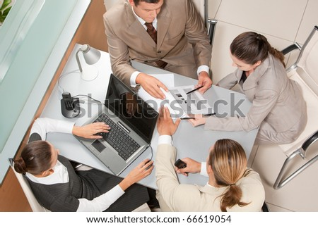 Above view of executive business group sitting at desk in office and busy working