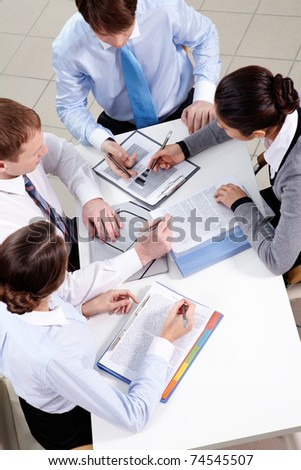 Above view of four businesspeople working businesspeople