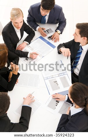 Above view of friendly team sharing ideas at meeting - stock photo
