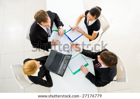 Above view of friendly workteam discussing business plans at meeting - stock photo