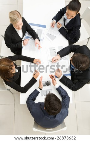 Above view of friendly workteam discussing new ideas at meeting