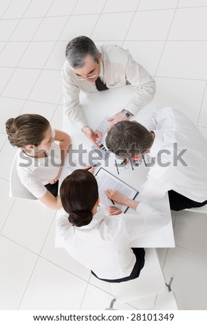 Above view of friendly workteam discussing new ideas at meeting - stock photo