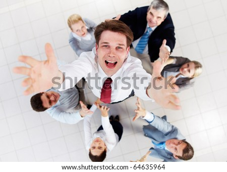 Above view of happy employer looking at camera while being thrown by several partners - stock photo