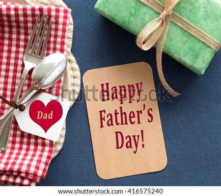Above view of Happy Father's Day Card and Place Setting with Dad name card, red and white napkin, silverware, navy placemat and green wrapped present.  Horizontal, almost square, with texture.