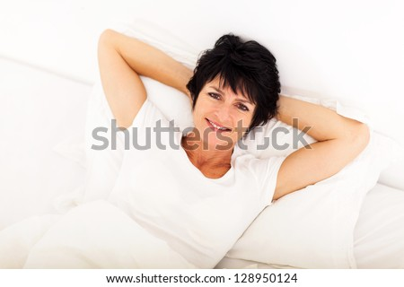 above view of happy middle aged woman lying on bed