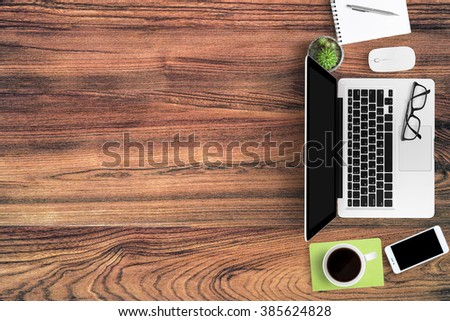 Above view of hipster wood office table full with gadgets and supplies with copy space. - stock photo