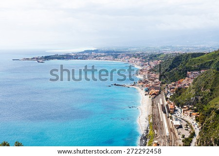 above view of Ionian Sea coastline and Giardini Naxos town from Taormina city, Sicily, Italy in spring - stock photo