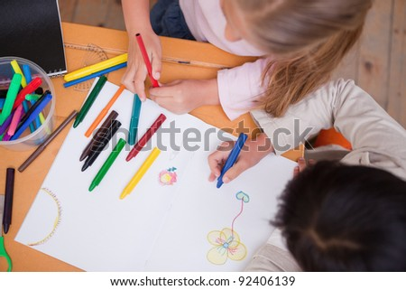 Above view of little schoolgirls drawing in a classroom - stock photo