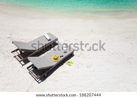 Above view of lounge chairs on a beautiful tropical beach at Maldives - stock photo