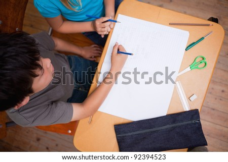 Above view of pupils working together in a classroom - stock photo