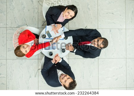 Above view of several business people are planning work at round table. They are looking at the camera. - stock photo