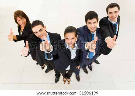 Above view of several successful partners looking at camera and showing thumbs up - stock photo