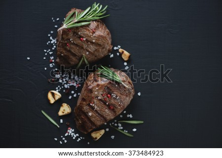 Above view of two grilled filet mignon beefsteaks, close-up, black wooden background