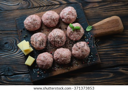 Above view of uncooked meatballs in a dark rustic wooden setting