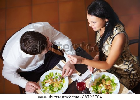 Above view of woman and man eating in cafe - stock photo
