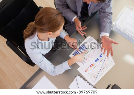 Above view of young business people analyzing statistics - stock photo