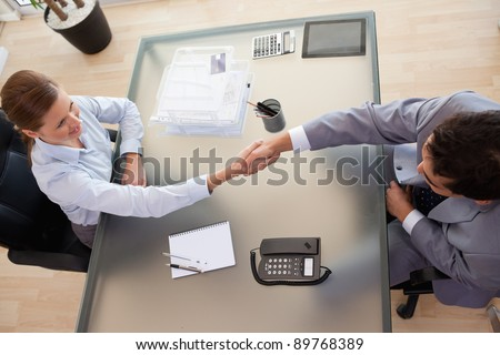 Above view of young consultant shaking hands with customer - stock photo