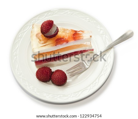 Above view over a section of layered jello pie with lychees on plate and dessert fork