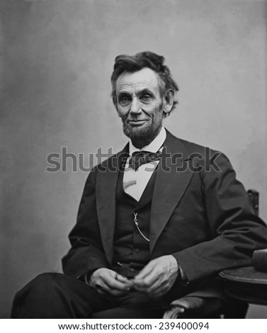 Abraham Lincoln (1809-1865) seated and holding his spectacles and a pencil on Feb. 5, 1865 in portrait by Alexander Gardner. - stock photo