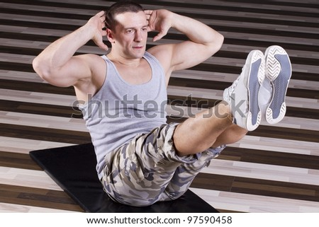 Abs exercise in the gym legs high above straight ahead - stock photo