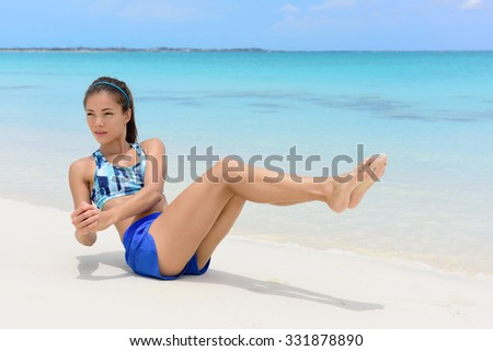 Abs workout - fitness woman working out on beach doing russian twists exercises with raised legs to tone body and train oblique muscles. - stock photo