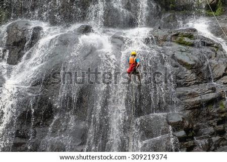Abseiling at Wangtum waterfall, Petchabun, Thailand - stock photo