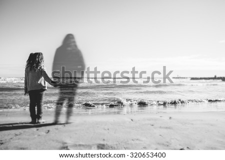 Absence: A girl holds the hand what appears to be the spirit of his dead mother. The image has been selectively blurred to give a touch of mystery  - stock photo