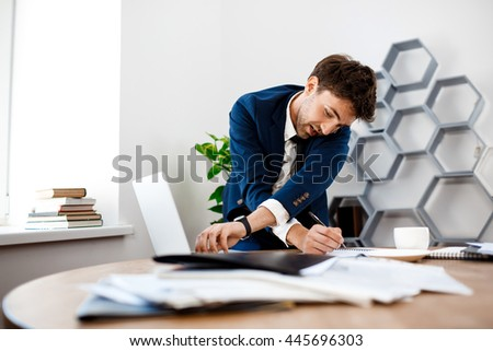 Absentminded young businessman speaking on phone, office background.