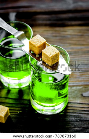 absinthe shots with sugar on wooden table background