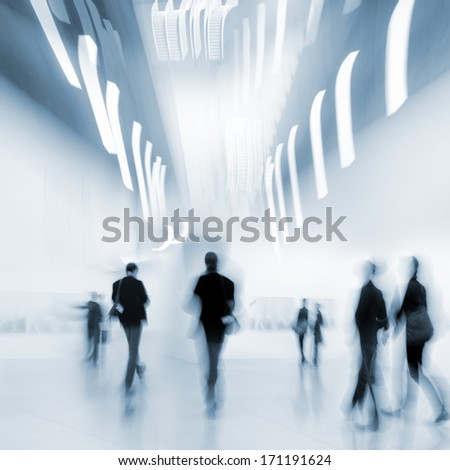 abstakt image of people in the lobby of a modern art center with a blurred background and blue tonality