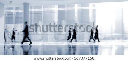 abstakt image of people in the lobby of a modern business center with a blurred background and  blue tonality  - stock photo