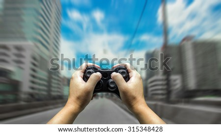 abstract action hand control racing with game joystick - stock photo