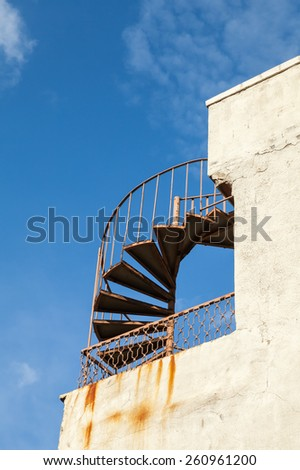 Abstract architecture fragment, old outdoor metal spiral ladder on the wall - stock photo
