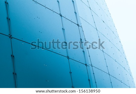 Abstract architecture fragment with blue wet steel panels - stock photo